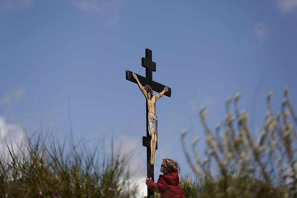 An boy kisses a crucifix on Good Friday at Penteli monastery, north of Athens