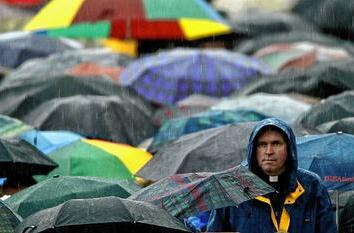 Rain beats down on a priest as he attends Pope John Paul II's general audience at the Vatican.