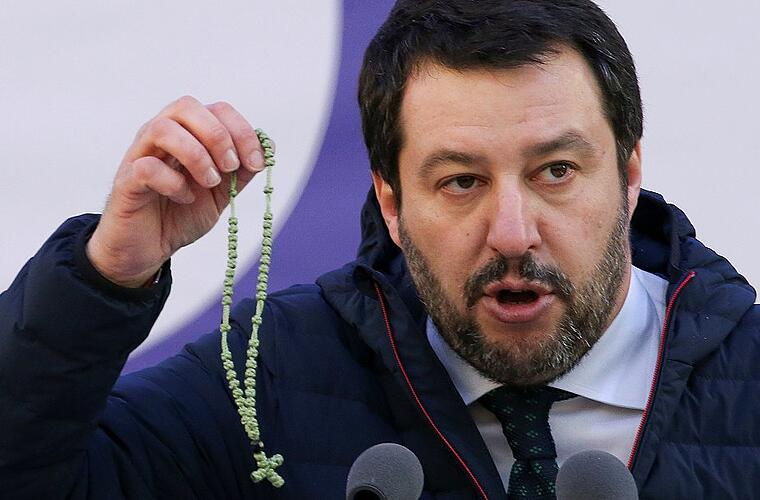Italian Northern League leader Matteo Salvini shows a rosary as he speaks during a political rally in Milan