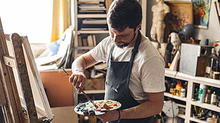 Male painter at art studio indoors with palette mixing colors ready to draw concentrated