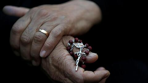 An Iraqi Christian woman holds a cross during a prayer session inside the Syriac Orthodox Church of Mart Shmoni during the Good Friday prayers in Erbil