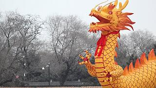 People gather next to a dragon-shaped lantern ahead of New Year celebrations at Beiling park in Shenyang