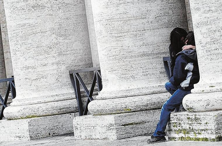 A couple kisses in Saint Peter's Square at the Vatican