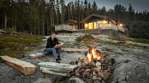 woman reading beside campfire in norway