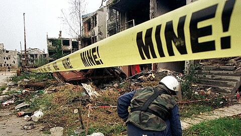 A Bosnian man searches for landmines in Sarajevo's suburb of Nedjarici October 27. Around 50 people ..