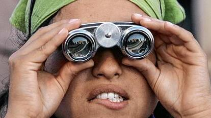 A young pilgrim uses binoculars to look at Pope Benedict at the Marienfeld.