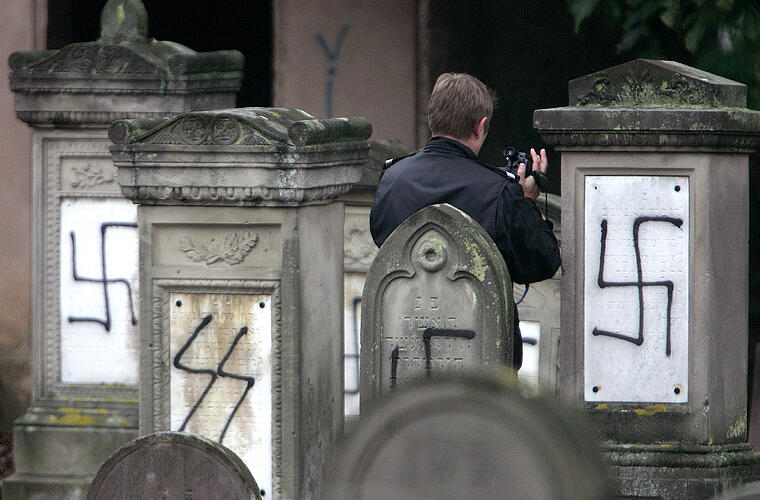 A French gendarme films tombstones desecrated by vandals with Nazi swastikas and anti-semitic slogan..