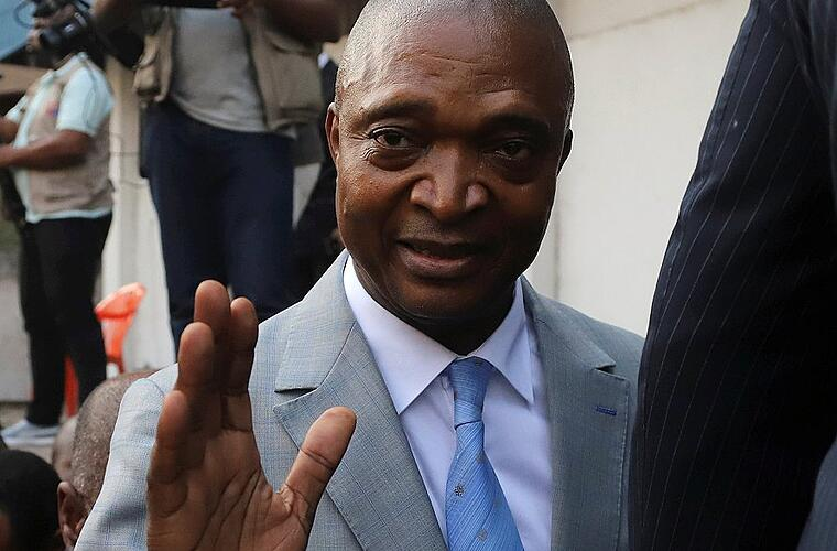 Former Congolese interior minister Emmanuel Ramazani Shadary waves to his supporters as he arrives to file his candidacy for the presidential election, at the Congo's electoral commission head offices in Kinshasa