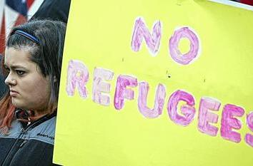 A protestor holds an anti-refugee sign to protest the United States' acceptance of Syrian refugees at the Washington State capitol in Olympia