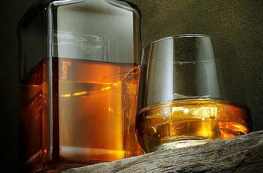 close up view of glass of  whiskey and a bottle aside