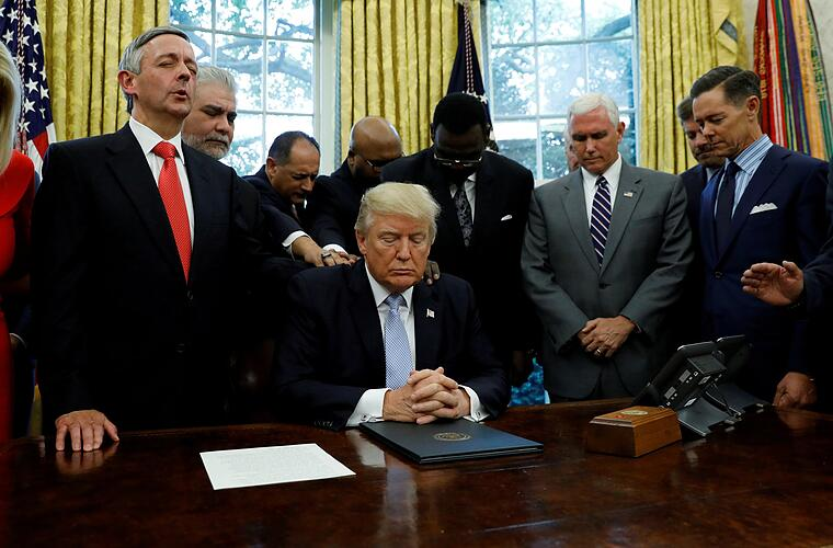 Faith leaders place their hands on the shoulders of U.S. President Donald Trump as he takes part in a prayer for those affected by Hurricane Harvey in the Oval Office of the White House in Washington