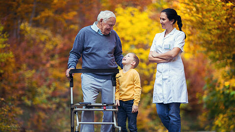 Young grandson spending time in the park with disabled senior grandfather
